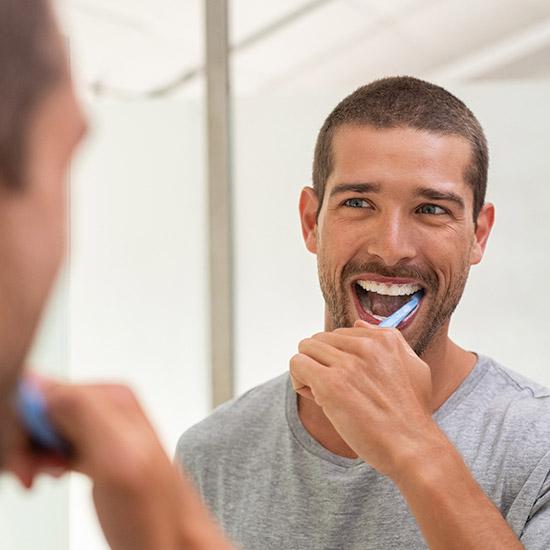 man brushing his teeth and looking in mirror